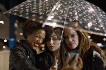 Girl friends going out at night under cute umbrella taking selfie