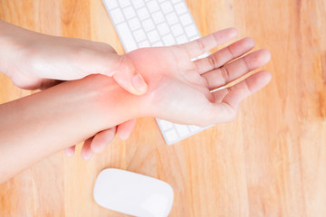Asian woman massaging painful hand, office syndrome concept