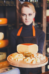 Cheese platter in shop assistant hands