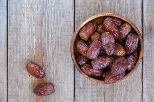 Fresh royal medjool dates in wooden bowl. Love for a healthy vegan food concept.
