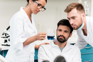 Professional young chemists in lab coats making working with reagent in laboratory