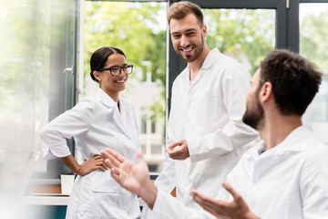 Team of professional scientists in white coats smiling and talking in laboratory