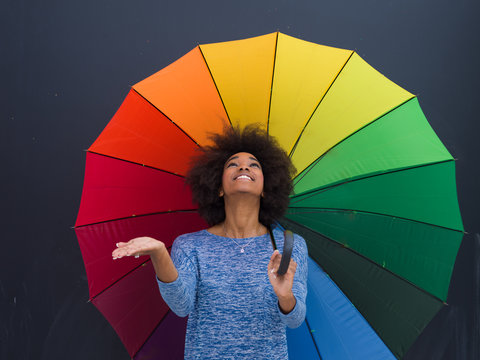 african american woman holding a colorful umbrella