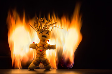 A voodoo doll stands in front of a fire