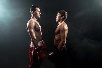 Two professional boxer standing on black smoky background,