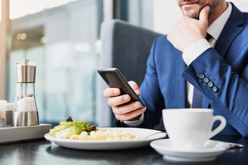 Confident businessman messaging on phone in restaurant