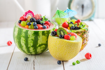 Fruits salad in melon and pineapple with berry fruits
