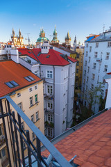A view from above on apartment houses in the city of Prague, Czech Republic. Roofs of buildings, churches and cathedrals of Prague. Vertical format of the frame.