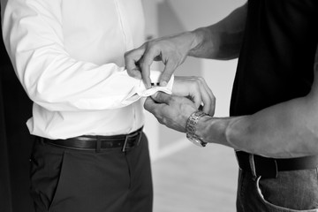 Groom helps the bride to dress elegant cufflinks. Black and white photo of male hands.