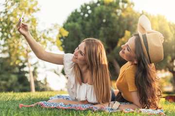 Beautiful women taking a selfie portrait in park.