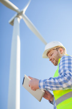 young engineer is checking on wind turbine energy production