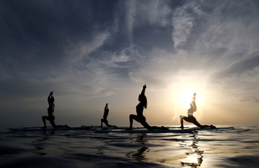 People practise standup paddleboard yoga, or SUP yoga, on the Adriatic coast in Verudela