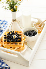 Healthy breakfast: Belgian waffles with blueberries, honey and milk decorated chamomile flowers on white wooden salver. Warm light. Selective focus