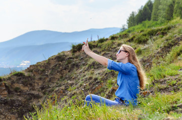 Young girl in blue clothes, wearing sunglasses doing selfie in summer outdoors