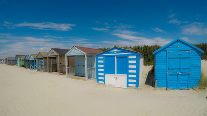 Traditional beach huts on fine golden sand at West Wittering Beach West Sussex England UK