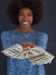 black woman holding money on gray background