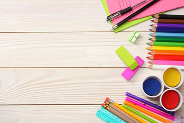 school and office supplies. school background. colored pencils, pen, pains, paper for  school and student education on white wooden background. top view with copy space