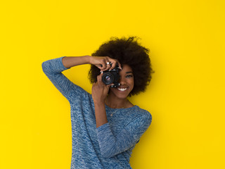young african american girl taking photo on a retro camera