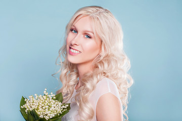 Closeup portrait of young beautiful blonde bride in spring style with bouquet of lily of the valley flowers on blue background. Wedding makeup and hairstyle in natural style. Just married
