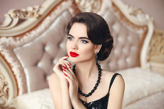 Beauty fashion woman model brunette, elegant lady portrait. Manicure nails. Hollywood red lips makeup, wavy hairstyle. Vintage Girl posing on modern sofa in luxury interior.