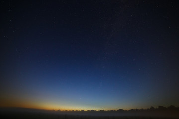 Stars of the Milky Way galaxy in the night sky. Space in the background of the morning dawn.