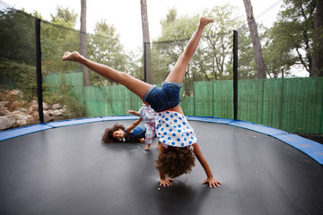 girl doing handstand on trampoline with siblings