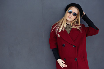 Stylish blonde with beautiful makeup in a red coat, hat and black glasses on the background of a gray wall