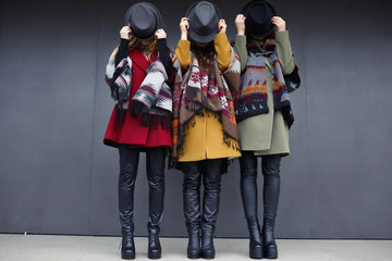 Stylish girls in fashionable cashmere coats of green, yellow and red, black glasses, scarf, and leather shoes on the background of a gray wall