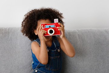 portrait of a girl playing with a toy camera