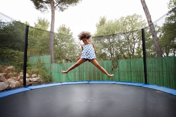 girl with afro hair bouncing on trampoline