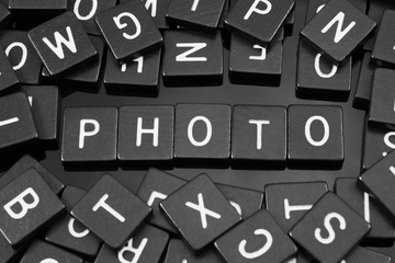 "Black letter tiles spelling the word ""photo"" on a reflective background"