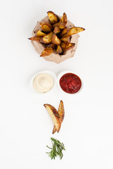 Baked potatoes with rosemary, tomato sauce and mayonnaise on white background..