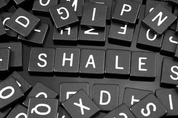 """Black letter tiles spelling the word """"shale"""" on a reflective background"""