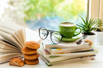 Coffee cup, open book, glasses, cookies and flower on window with bokeh. Reading and breakfast. Concept warm and cozy home interior