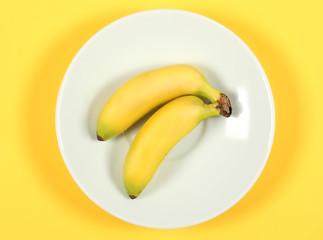банан фрукт лежит на белой тарелке на жёлтом фоне