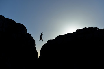 man who jumped on the rocks in silhouette