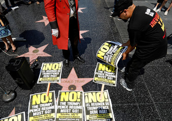 An activist places signs on the star of Donald Trump on the Hollywood Walk of Fame during a news conference to announce nationwide protests in Los Angeles