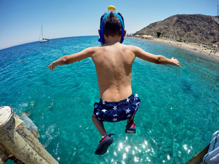 The boy is jumping into the sea