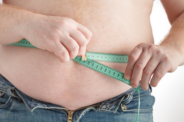 fat man check out his body fat with measuring tape for fat or obesity background