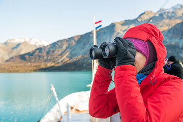 Wall Mural - Tourist looking at Alaska Glacier Bay landscape using binoculars on cruise ship. Woman on vacation travel looking for wildlife enjoying cruising famous tourist destination.