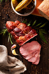 Smoked ham sliced on a wooden rustic table with addition of fresh aromatic herbs, top view.