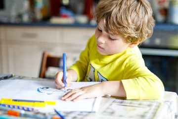 Adorable preschool kid boy painting with colorful pencils police car