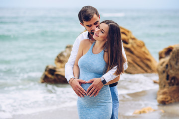 Loving couple making a heart shape on the pregnant belly with their hands.