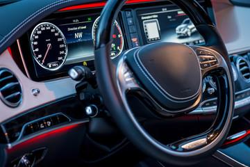 Auto. Luxury car steering wheel and dashboard