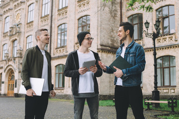 Successful happy students standing near campus or university outside