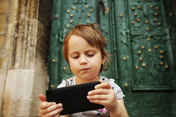Little beautiful child girl using smartphone as symbol of work. Connect to the Internet with smartphone. (Development, education, technology concept)