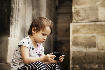 Little beautiful child girl using smartphone as symbol pf work or study. Connect to the Internet with smartphone. (Development, education, technology concept)