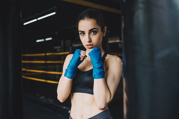 Beautiful and fit female fighter getting prepared for the fight or training
