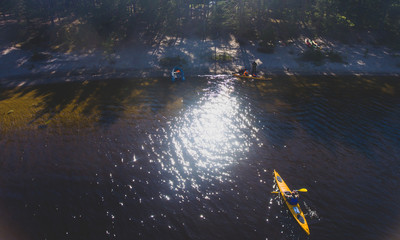 A group of kayakers in the lake skerries on the with colorful canoe kayak boat, shot from drone
