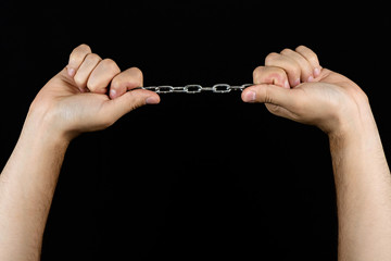 Male hands holding a stretched chain isolated on black background
